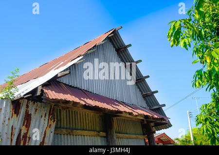old rusty galvanized sheet (zinc sheet) building with green tree and blue sky. - Stock Photo