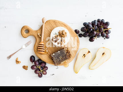 Camembert cheese with grape, walnuts, pear and honey on oak serving board - Stock Photo