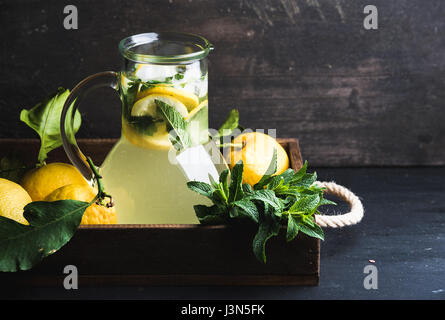 Homemade mint lemonade served with fresh lemons and ice over wooden background, top view, copy space - Stock Photo