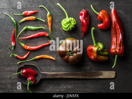 Red and green vegetables with rustic old spoon on dark wooden background, top view - Stock Photo