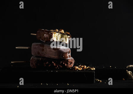 Stack of chocolate dipped popsicles with chipped nuts on dark wooden board over black background. - Stock Photo