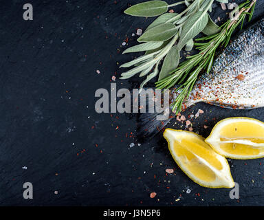 Tail of fresh raw Dorado or sea bream fish on black slate stone board with spices, herbs, lemon and salt - Stock Photo