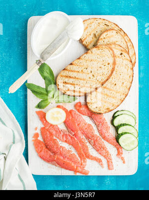 Ingredients for healthy sandwich. Grilled bread slices, smoked salmon, cottage cheese, cucumber and basil on white - Stock Photo