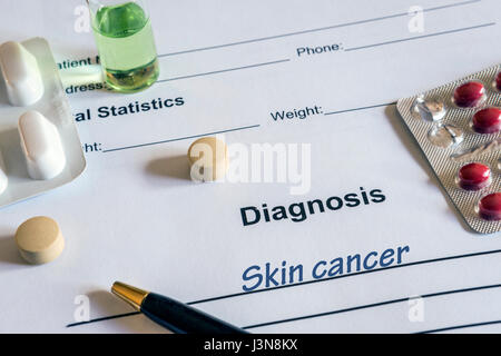 Diagnosis skin cancer written in the diagnostic form and pills - Stock Photo