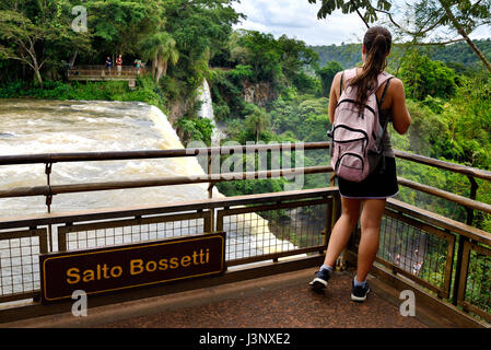 Young female tourist watching at Iguazu Falls (aka Iguassu Falls or Cataratas del Iguazu), Misiones Province, Argentina - Stock Photo