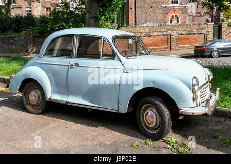 Slightly dilapidated light blue two-door Morris Minor 1000 classic car in Hampstead, London, UK - Stock Photo