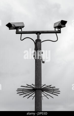 Security CCTV cameras mounted on a tall metal pole with anti-climb device - Stock Photo