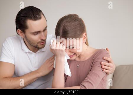 Husband comforting sad crying wife, man consoling sobbing young  - Stock Photo