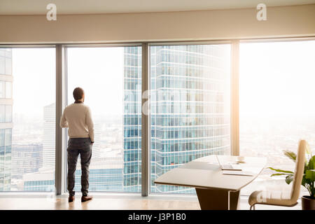 Young successful businessman standing in office looking at full- - Stock Photo