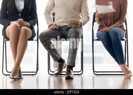 Group of people waiting for job interview, sitting on chairs - Stock Photo