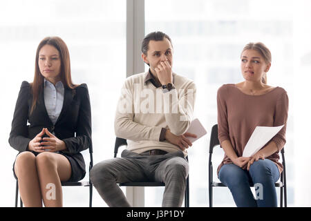 Business people group sitting on chairs waiting, expressing diff - Stock Photo