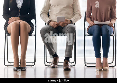 Applicants waiting for job interview, sitting on chairs and prep - Stock Photo