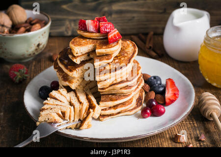 Healthy pancakes. Stack of delicious healthy whole grain pancakes with spelt flour served with strawberries, blueberries, - Stock Photo