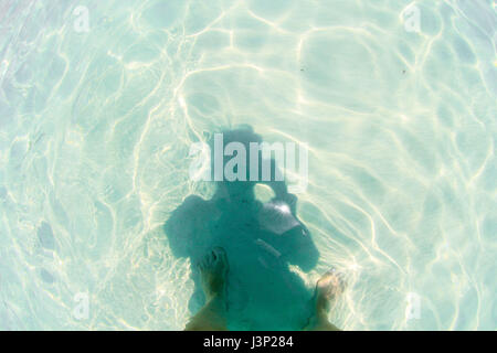 Shadow, self-portrait, on vacation. Crystal clear ocean water, sunshine and feet. - Stock Photo