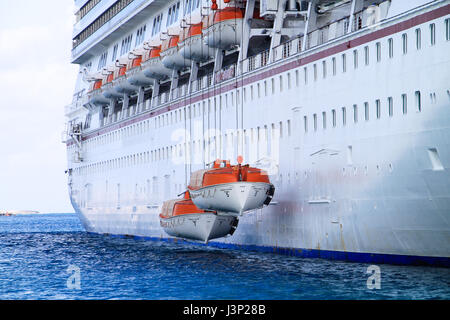 A large passenger ship is seen doing safety drills with its life rafts. - Stock Photo