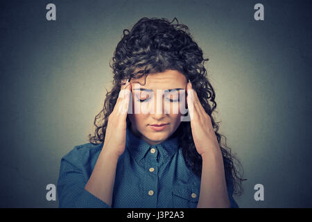 Closeup sad young woman with worried stressed face expression having headache isolated on gray wall background. - Stock Photo