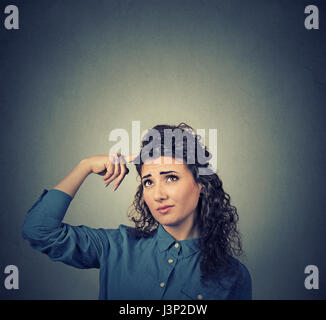 Portrait closeup confused skeptical young woman thinking looking up isolated on gray wall background copy space - Stock Photo