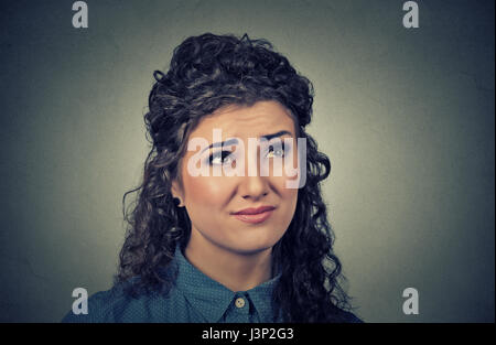 Portrait closeup confused skeptical young woman thinking looking up isolated on gray wall background. Human expressions, - Stock Photo
