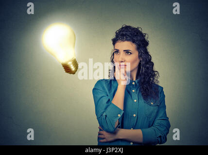 Closeup beautiful girl thinks looking up at bright light bulb isolated on gray wall background. Idea, education - Stock Photo