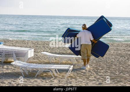 Miami Beach Florida Atlantic Ocean sand shore public beach rental lounge chair cushions Hispanic man attendant job - Stock Photo