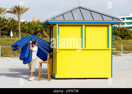 Miami Beach Florida sand shore public beach rental lounge chair cushions Hispanic man attendant job working guest - Stock Photo
