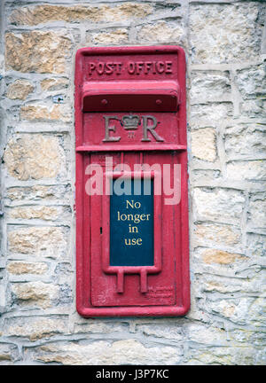 CASTLE COMBE, UK - MAY 5, 2017: Main street in Castle Combe, Wiltshire, UK,  showing old disused post office box - Stock Photo