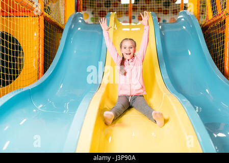 Smiling girl riding from childrens slides on playground, attraction in game center. Happy childhood. Adventure time - Stock Photo
