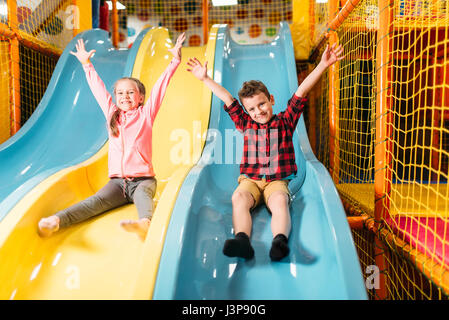 Little kids riding from childrens slides in game center. Happy childhood. Adventure time - Stock Photo