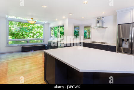Kitchen more functional with a sink, cooktop, refrigerator and partially installed vent hood. Window seat bench - Stock Photo