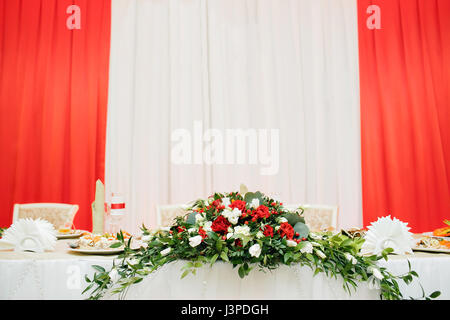 Wedding flowers of white and red roses on table of newlyweds. - Stock Photo