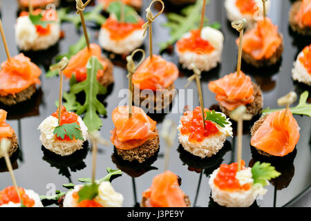 the buffet at the reception. Assortment of canapes. Banquet service. catering food, snacks with salmon and caviar. - Stock Photo