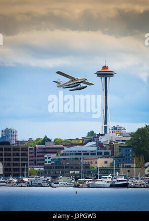 Seaplane taking off from Seattle's Lake Union with Space Needle in background - Stock Photo