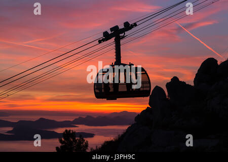 The cable car which shuttles tourists from Dubrovnik's old town to the peak of Srd Hill captured at sunset. - Stock Photo