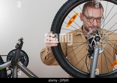 Bearded man puts the front wheel with hydraulic disc brake on the mtb bicycle. - Stock Photo