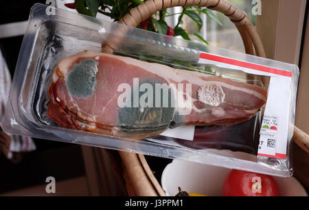 Shop bought bacon that has gone off and turned mouldy after sell by date expired - Stock Photo