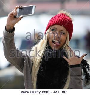 LOS ANGELES - APRIL 2017 —Blonde woman wearing red woolen hood  taking selfie with smartphone and extending her - Stock Photo