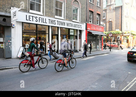 People tourists couple cycling past Cass Art shop on Santander Bikes bicycles on Wardour Street Soho in London UK - Stock Photo