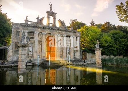 Valsanzibio sun rays pass through the gates of Valsanzibio garden on water pond entrance of Villa Barbarigo - Stock Photo
