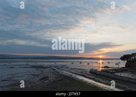 Sunset over the River Exe estuary seen from Lympstone towards Starcross & figure on harbour wall - Stock Photo