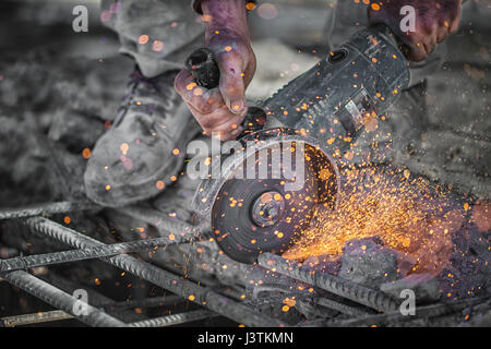Construction worker cuts hollow steel square tube with circular saw - Stock Photo