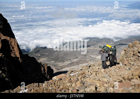 Two porters above the clouds climbing the Western Breach, Kilimanjaro National Park, Tanzania - Stock Photo