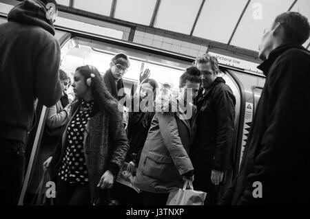 Commuters exiting Victoria Line train at Highbury & Islington station, north London. - Stock Photo