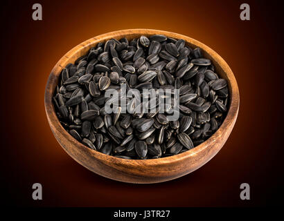 Black Sunflower seeds in wooden bowl isolated - Stock Photo
