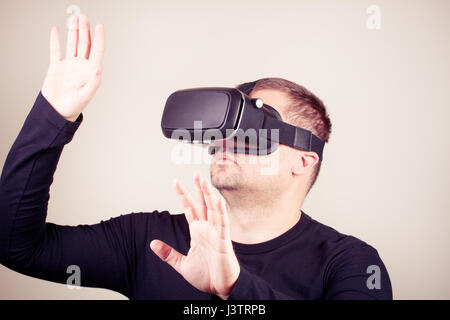 Young man using a virtual glasses on white background - Stock Photo
