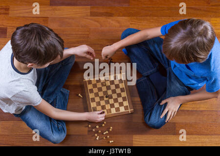 Kids playing chess sitting on wooden floor. Game, education, leisure concept. Top view. - Stock Photo