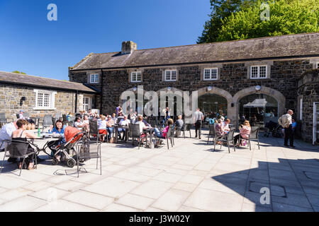 Lots of people outside the café at Clotworthy House, Antrim Castle Gardens, Northern Ireland, during a sunny day. - Stock Photo