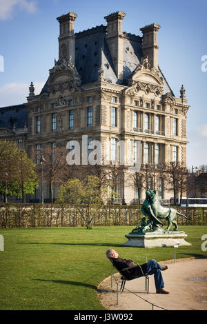 Tourist is relaxing on a bench In the park in front of the Louvre. View from Avenue du General Lemonnier to Jardin - Stock Photo