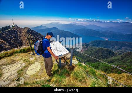 Hiker on  Monte Generoso mountain looking at Lugano city, San Salvatore mountain and Lugano lake, Canton Ticino, - Stock Photo