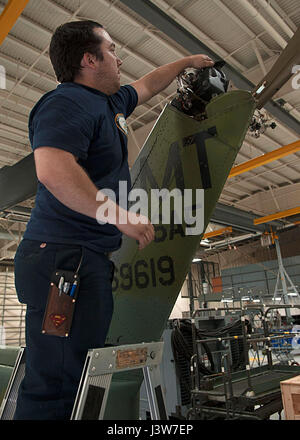 Thomas Martinez, 54th Helicopter Squadron aircraft mechanic, prepares to drain oil from a gear box at Minot Air - Stock Photo