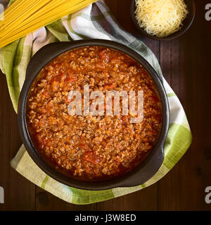 Homemade bolognese sauce made of fresh tomatoes, onion, carrot, garlic and mincemeat served in rustic bowl - Stock Photo